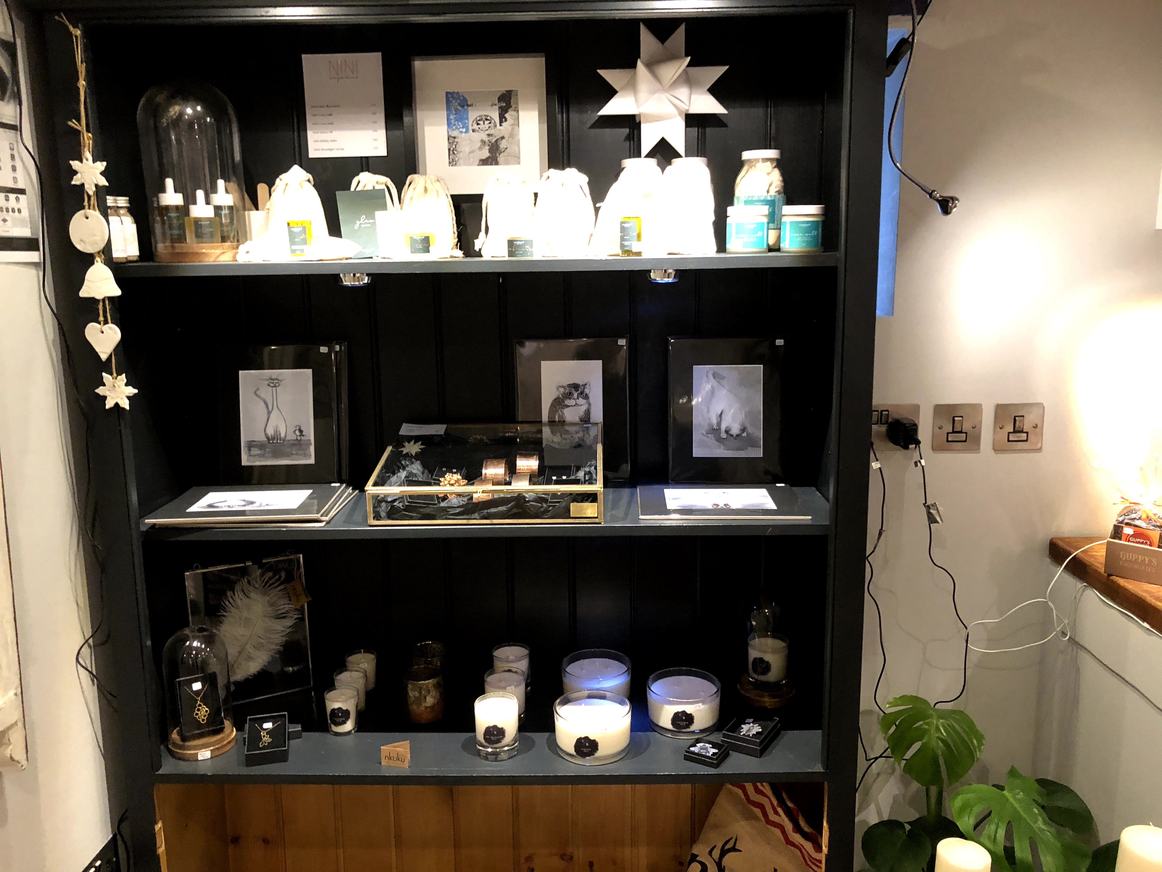 photo of shelves with jars, prints, and candles