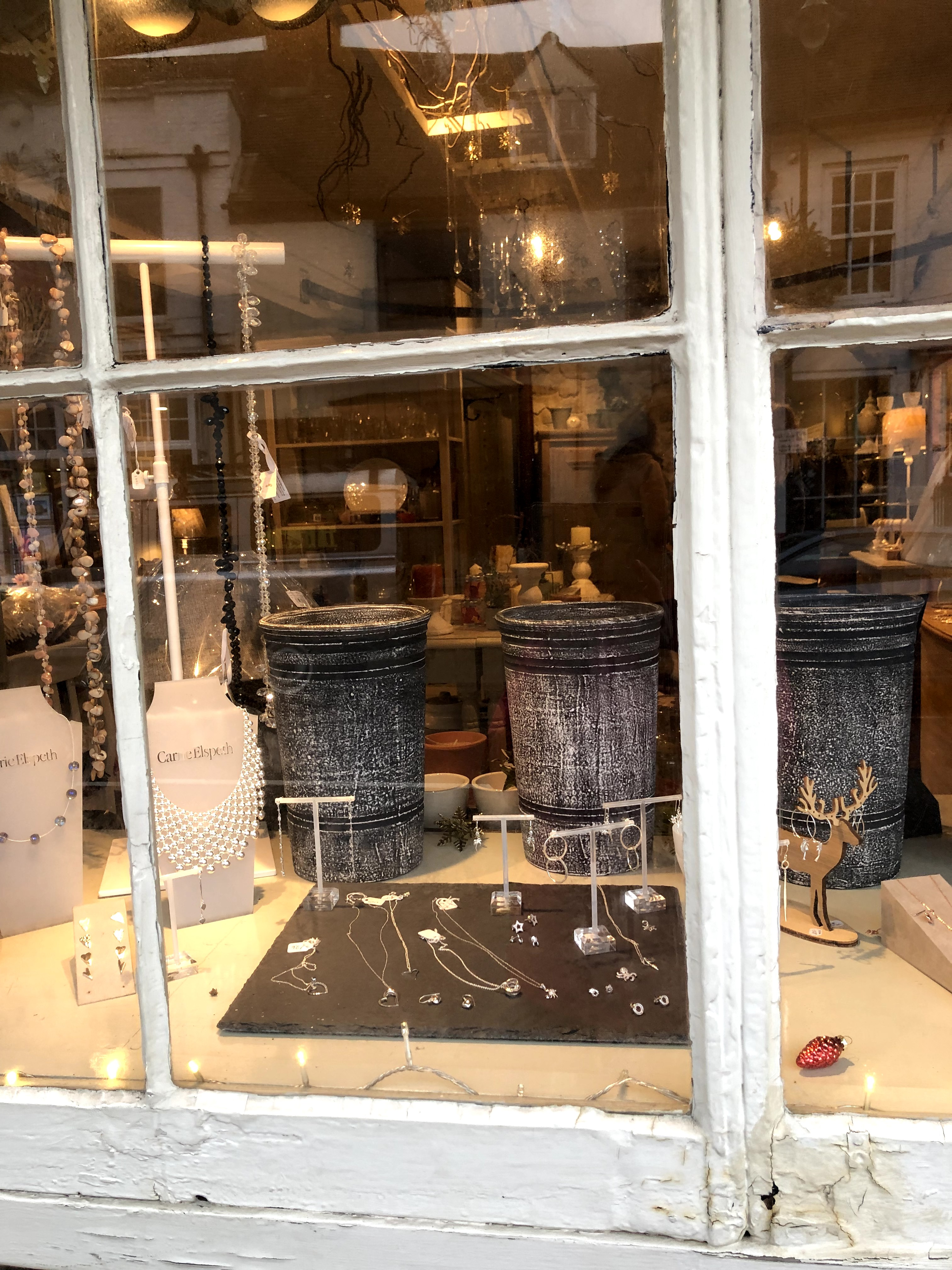 shop front with large grey vases
