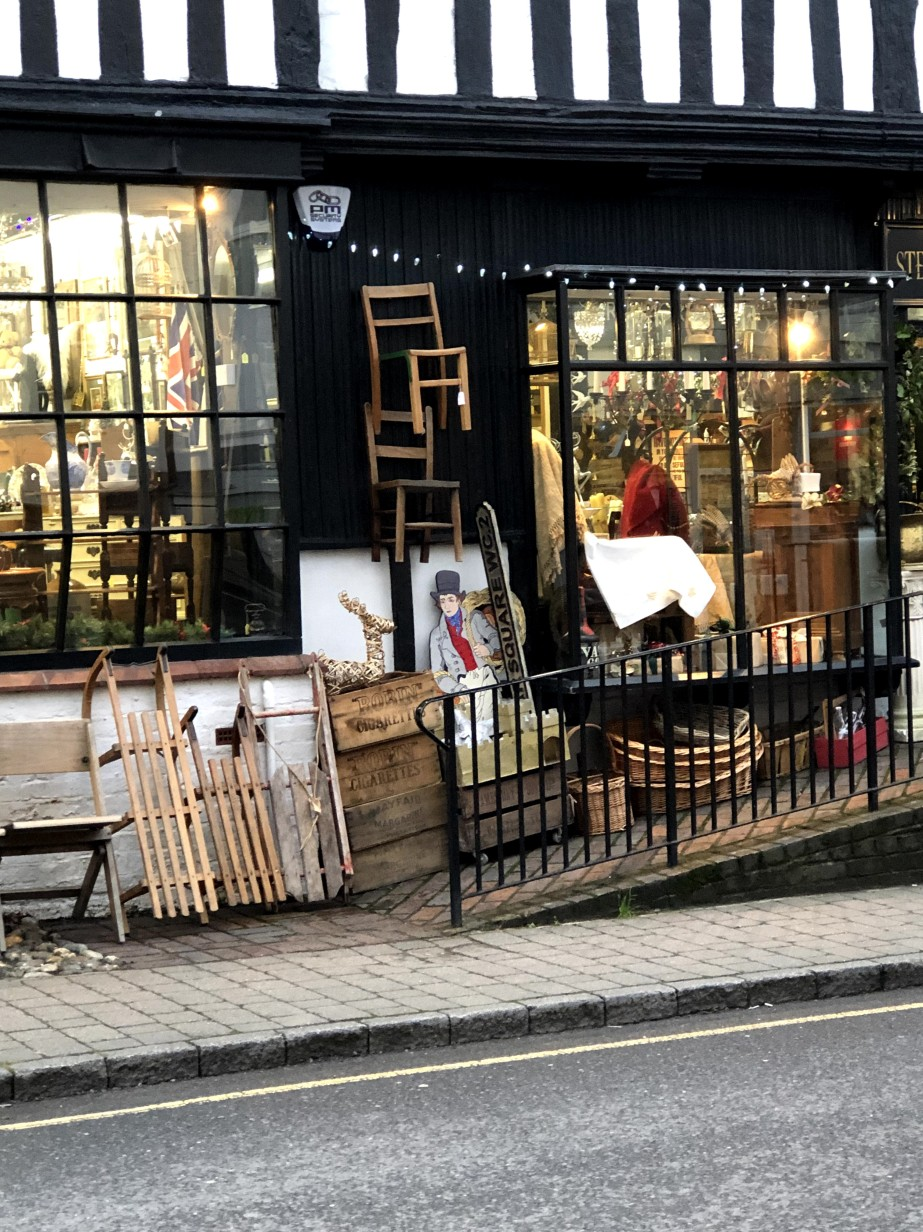 shop front with items on the pavement and lights over the windows